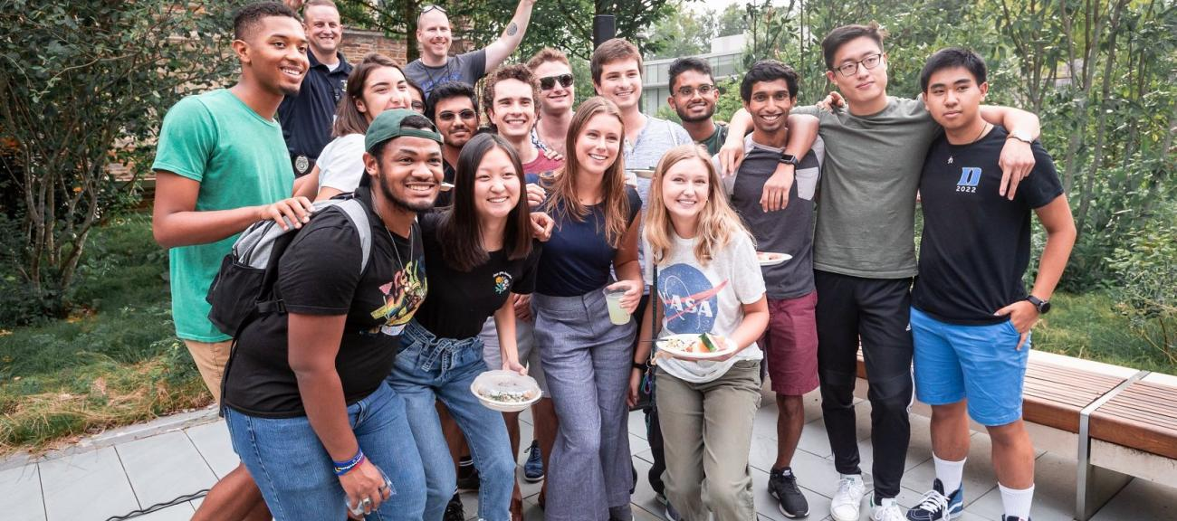 A group of students post for a photo with their arms around each other outside on Duke's campus