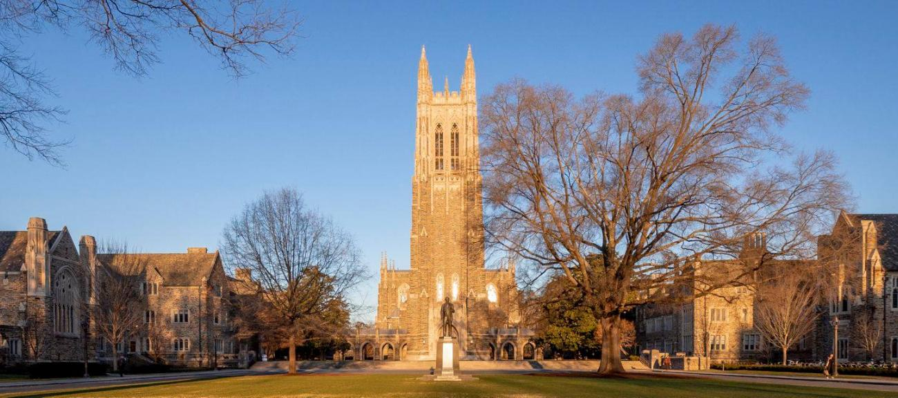 A wide view of Duke Chapel and Chapel Quad seen at sunset with golden light on the buildings.
