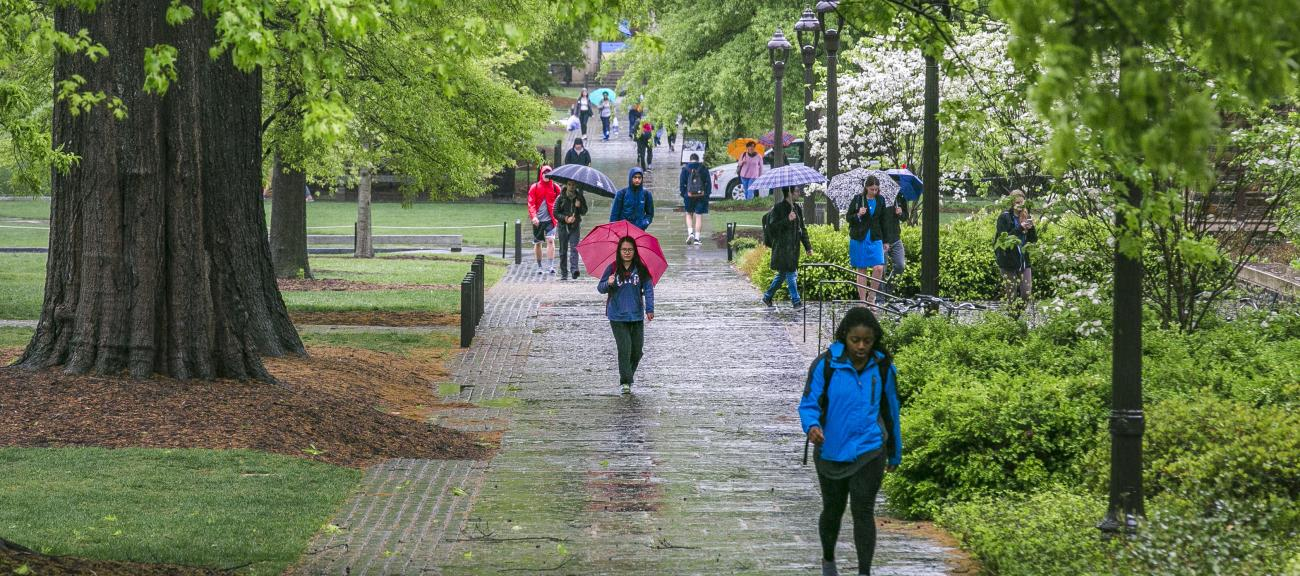students walking in the rain through the main west campus quad at Duke