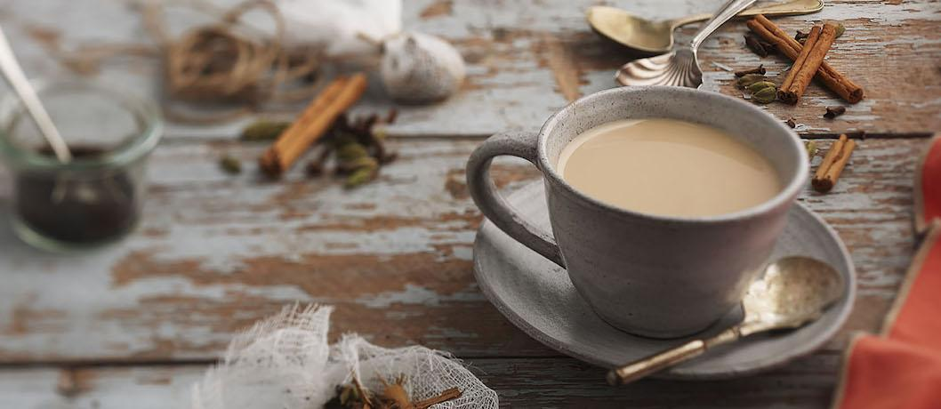 white tea cup with milky chai on a table with cinnamon sticks, anise, loose leaf tea, and other spices