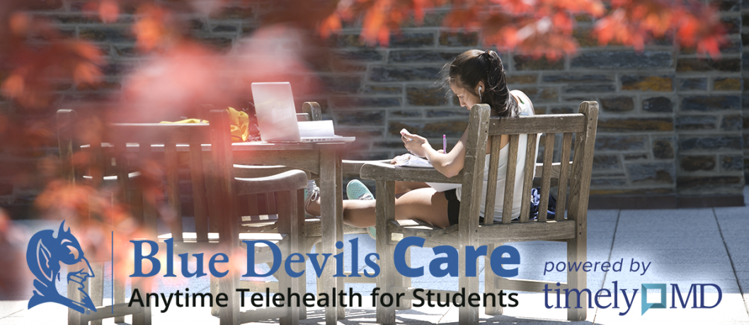 Student working at an outdoor table on a fall day, with Blue Devils Care logo across bottom