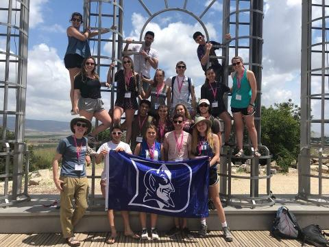 Students pose with a Duke flag on a Birthright Israel trip.
