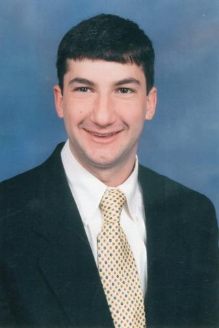 Class portrait of Erik Ludwig, who graduated from Duke in 1998, on a light blue background