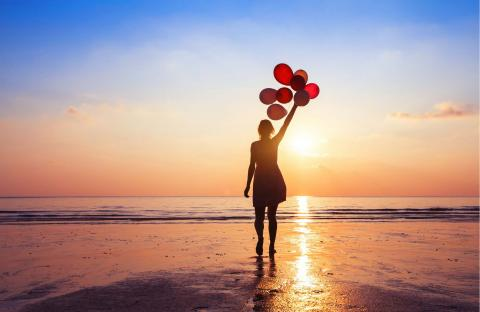 person walking on beach at sunrise with balloons