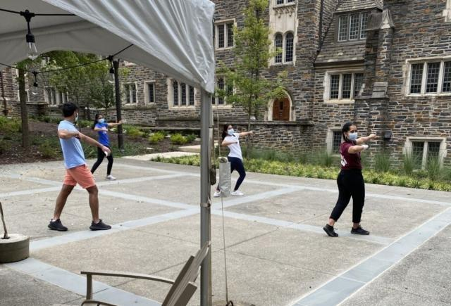 four students wearing masks practicing a dance routine on east campus