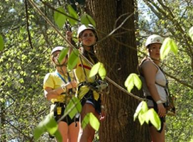 Three students in hard hats on a ropes course