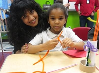 College student helping a little girl make art with pipe cleaners