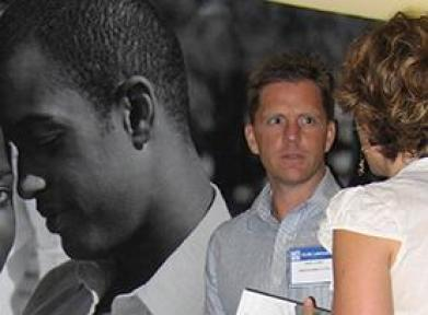 Man and woman talking in front of a poster at a career fair