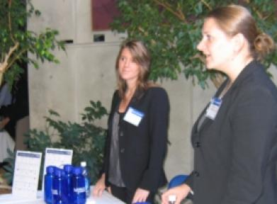 Two women in blazers at a career fair table